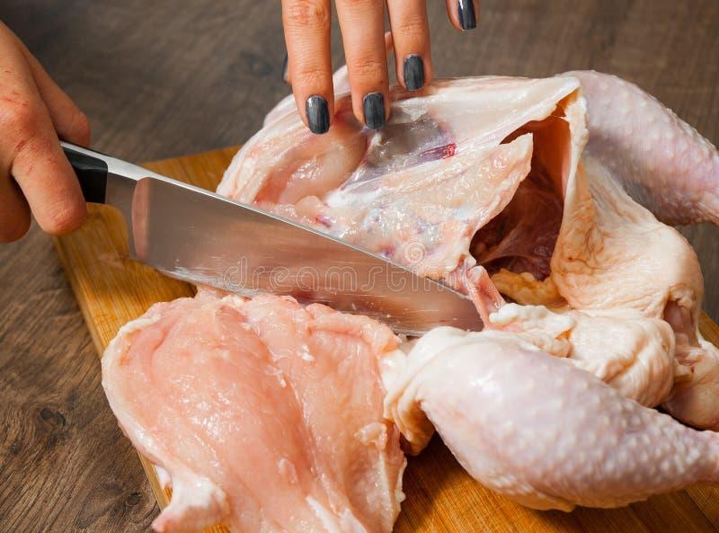 Le chef remet la carcasse de coupes de femme du poulet entier sur un fond en bois photographie stock libre de droits