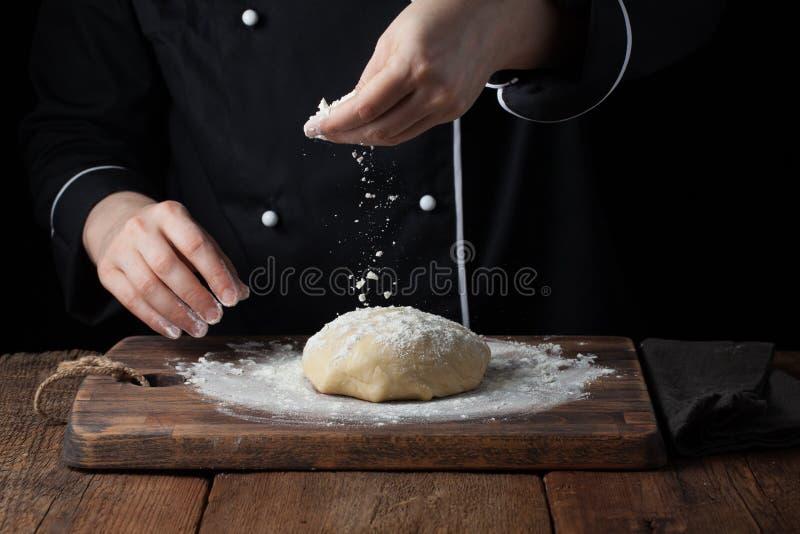 Le chef remet la poudre de versement de farine sur la pâte crue utilisant le tamis sur un fond noir, procédé de cuisson photographie stock libre de droits