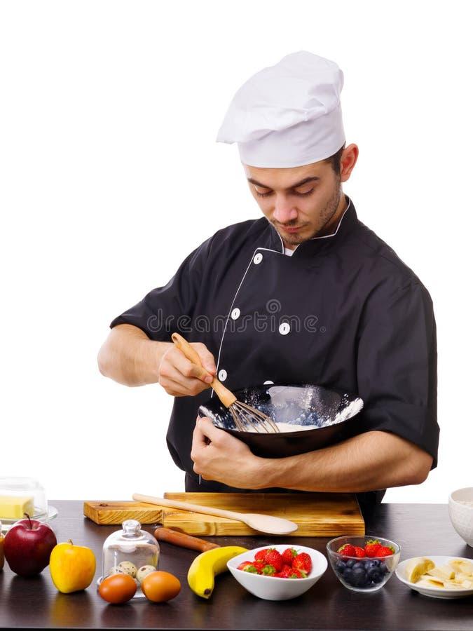 Le chef remuant un mélange de battage dans une cuvette au-dessus d'une table sur un blanc a isolé le fond photos stock