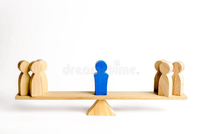 Le chef se tient sur les échelles entre deux groupes de personnes Situations de résolution de conflit L'union de deux groupes de  image stock
