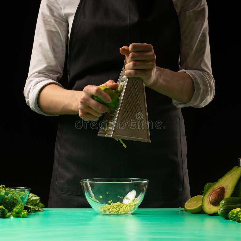 Le chef sur un fond noir frotte l'avocat pour faire cuire le smoothie vert de detox Nourriture saine et propre, concept de perte  photo stock