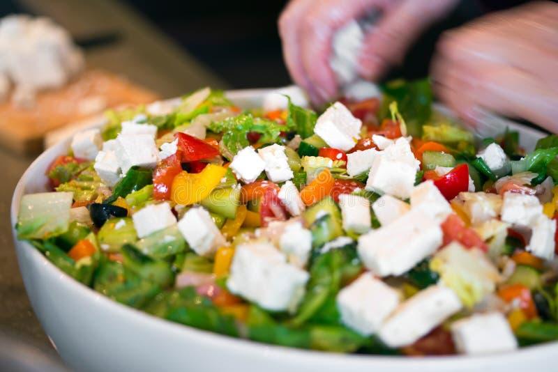 Le chef verse le fromage découpé dans la salade diététique fraîche des beaucoup h images stock