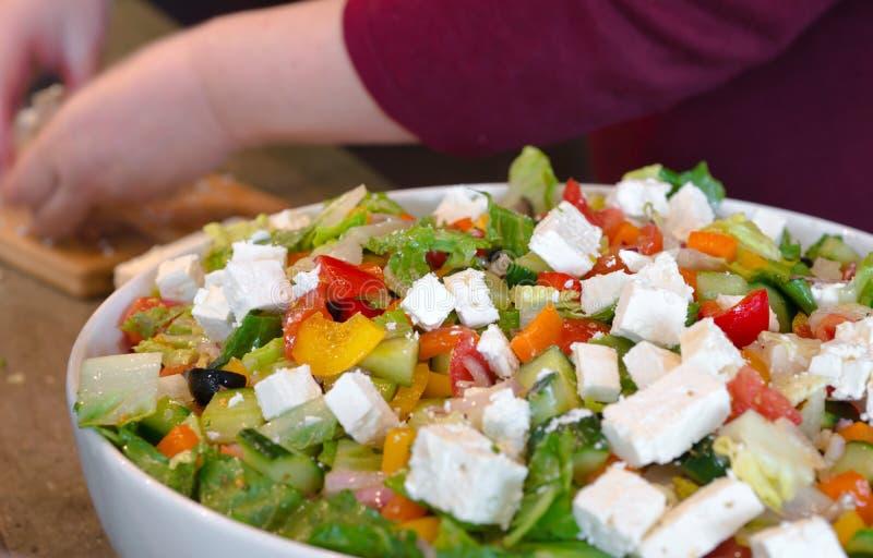 Le chef verse le fromage découpé dans la salade diététique fraîche des verts a photos libres de droits