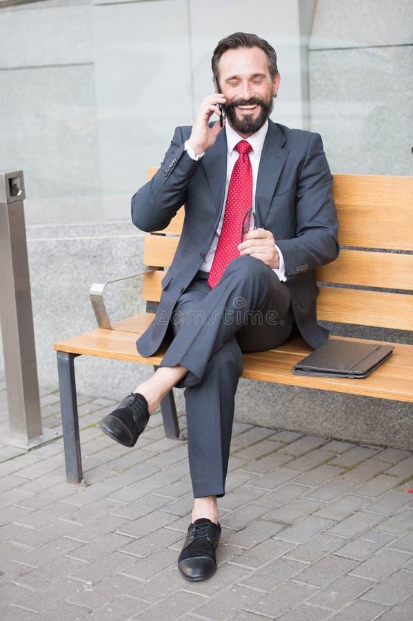 Le chefsammanträde på bänk och ringa Stilig le ung affärsman som placerar på bänk med hans bärbar dator bredvid kontor arkivfoton