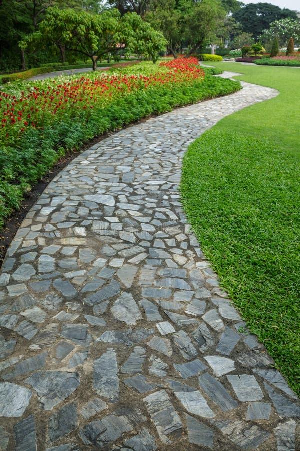 le chemin en pierre de promenade de bloc en stationnement avec l 39 herbe verte et le flowe image. Black Bedroom Furniture Sets. Home Design Ideas