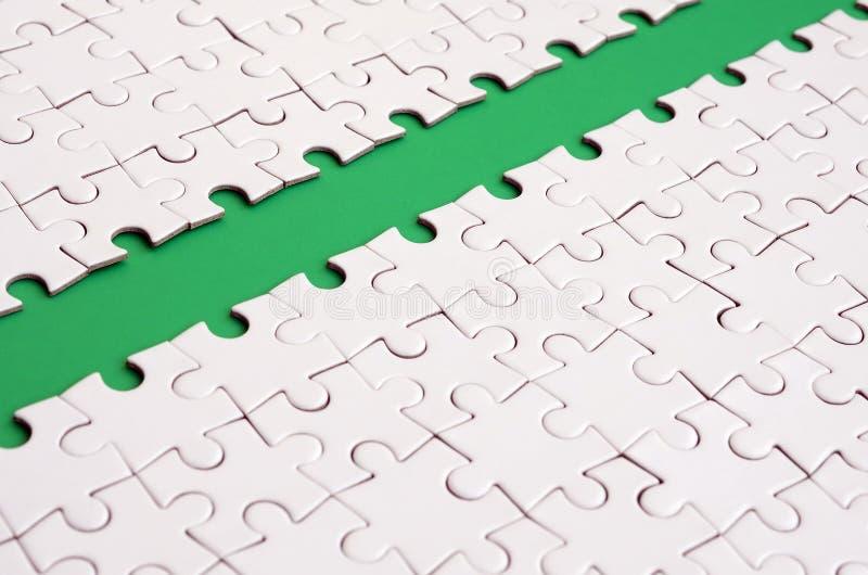 Le chemin vert est étendu sur la plate-forme d'un puzzle denteux plié par blanc Image de texture avec l'espace de copie pour le t photographie stock libre de droits