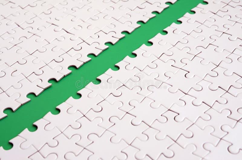 Le chemin vert est étendu sur la plate-forme d'un puzzle denteux plié par blanc Image de texture avec l'espace de copie pour le t image stock