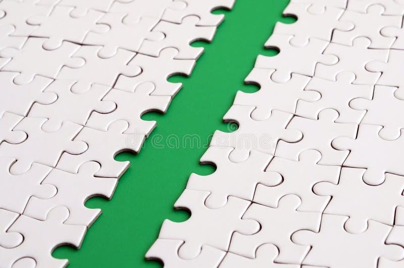 Le chemin vert est étendu sur la plate-forme d'un puzzle denteux plié par blanc Image de texture avec l'espace de copie pour le t photo stock
