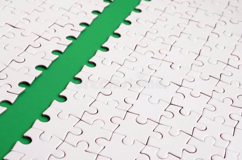 Le chemin vert est étendu sur la plate-forme d'un puzzle denteux plié par blanc Image de texture avec l'espace de copie pour le t images stock