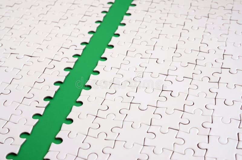 Le chemin vert est étendu sur la plate-forme d'un puzzle denteux plié par blanc Image de texture avec l'espace de copie pour le t photo libre de droits
