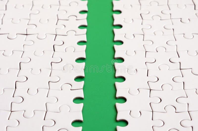 Le chemin vert est étendu sur la plate-forme d'un puzzle denteux plié par blanc Image de texture avec l'espace de copie pour le t photos stock