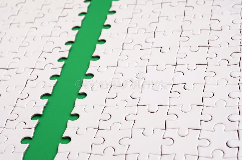 Le chemin vert est étendu sur la plate-forme d'un puzzle denteux plié par blanc Image de texture avec l'espace de copie pour le t images libres de droits