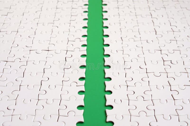 Le chemin vert est étendu sur la plate-forme d'un puzzle denteux plié par blanc Image de texture avec l'espace de copie pour le t photos libres de droits
