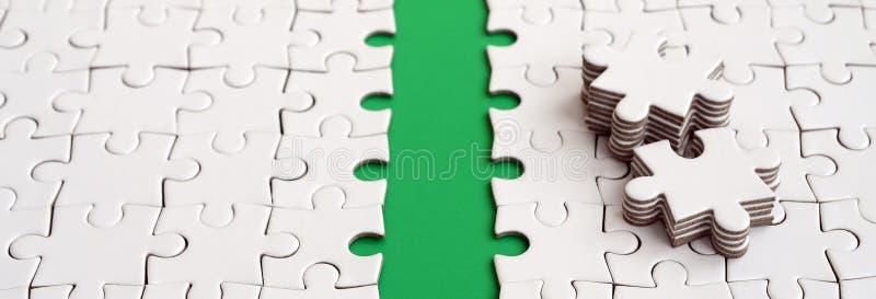 Le chemin vert est étendu sur la plate-forme d'un puzzle denteux plié par blanc Les éléments absents du puzzle sont empilés tout  photos stock