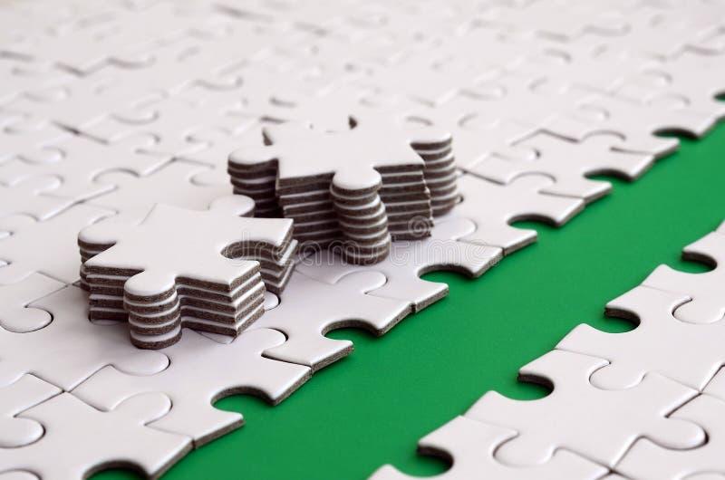 Le chemin vert est étendu sur la plate-forme d'un puzzle denteux plié par blanc Les éléments absents du puzzle sont empilés tout  image stock