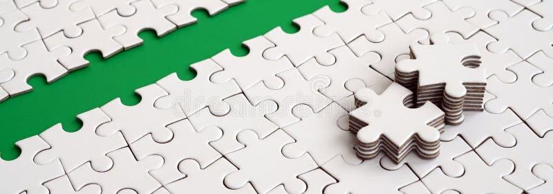 Le chemin vert est étendu sur la plate-forme d'un puzzle denteux plié par blanc Les éléments absents du puzzle sont empilés tout  images stock