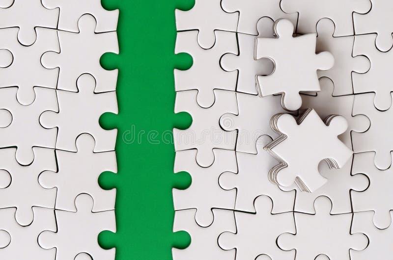 Le chemin vert est étendu sur la plate-forme d'un puzzle denteux plié par blanc Les éléments absents du puzzle sont empilés tout  images libres de droits
