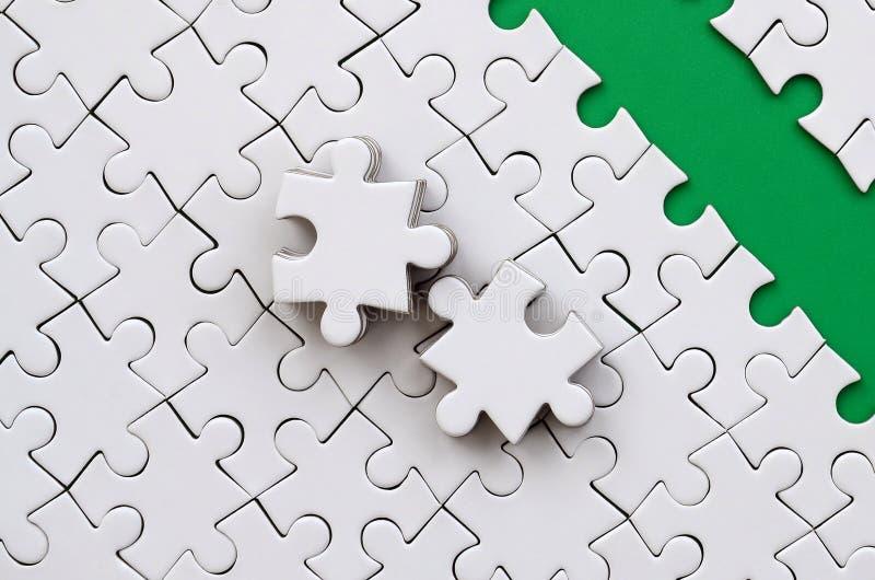 Le chemin vert est étendu sur la plate-forme d'un puzzle denteux plié par blanc Les éléments absents du puzzle sont empilés tout  photo libre de droits