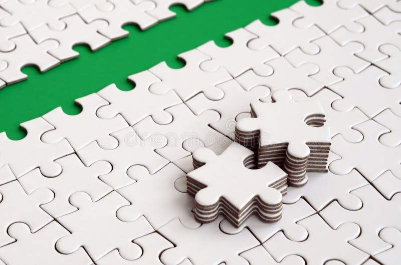 Le chemin vert est étendu sur la plate-forme d'un puzzle denteux plié par blanc Les éléments absents du puzzle sont empilés tout  image libre de droits