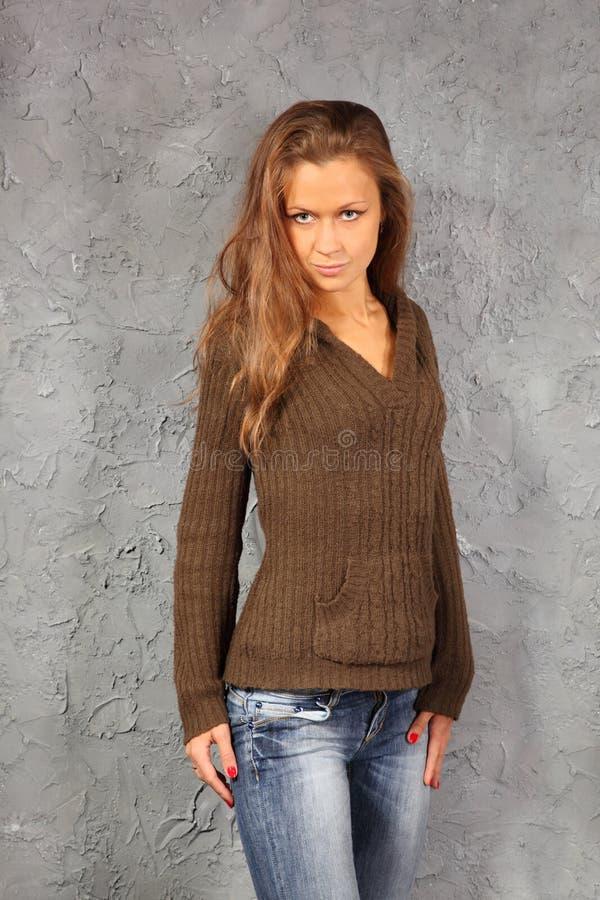 Le chemisier et les jeans s'usants de fille restent le mur proche photographie stock libre de droits