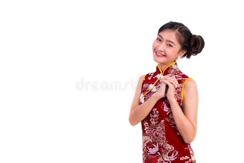 Le cheongsam de port et la bénédiction de jeune femme asiatique de beauté ou saluent photographie stock