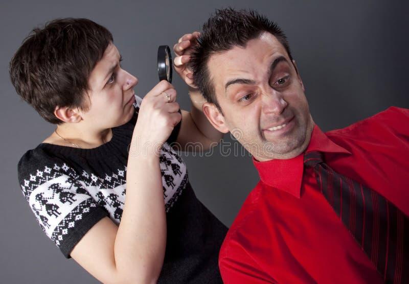 Le cheveu de l'homme de examen de femme photos stock