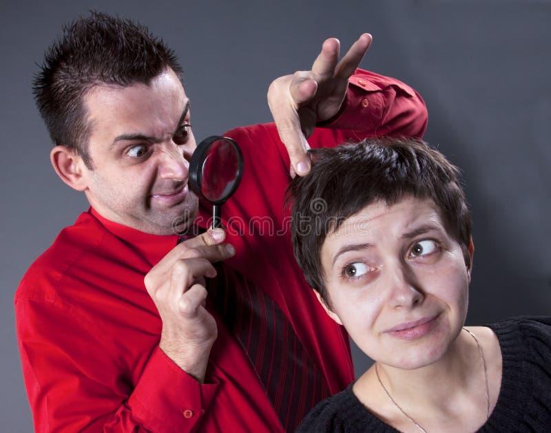Le cheveu de la femme de examen d'homme photographie stock libre de droits