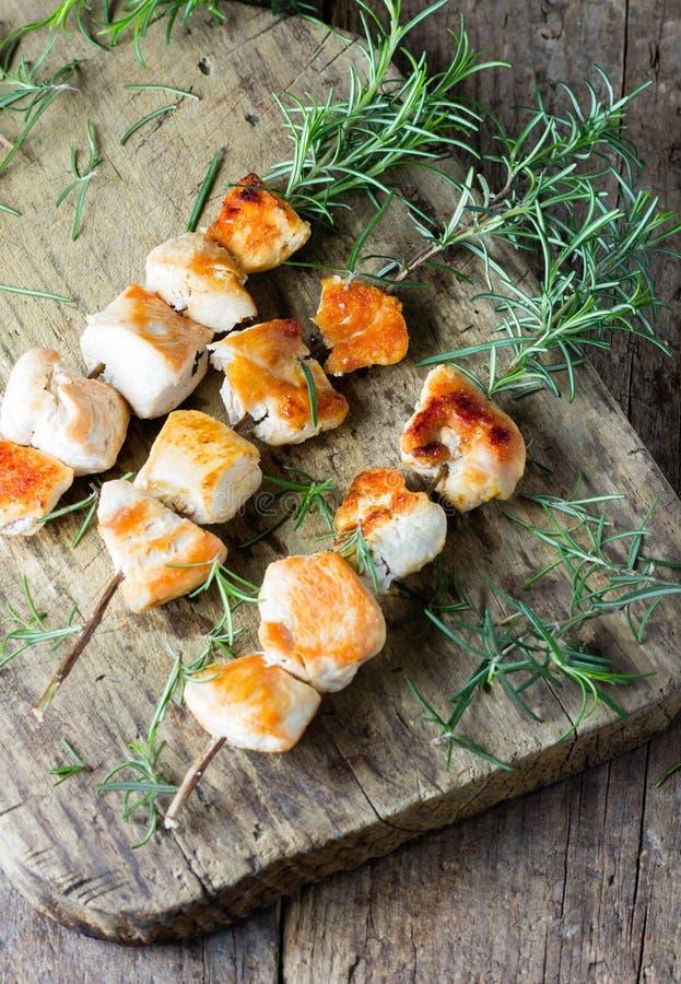 Le chiche-kebab de brochette de poulet a grillé la viande de BBQ sur la branche de romarin photo libre de droits