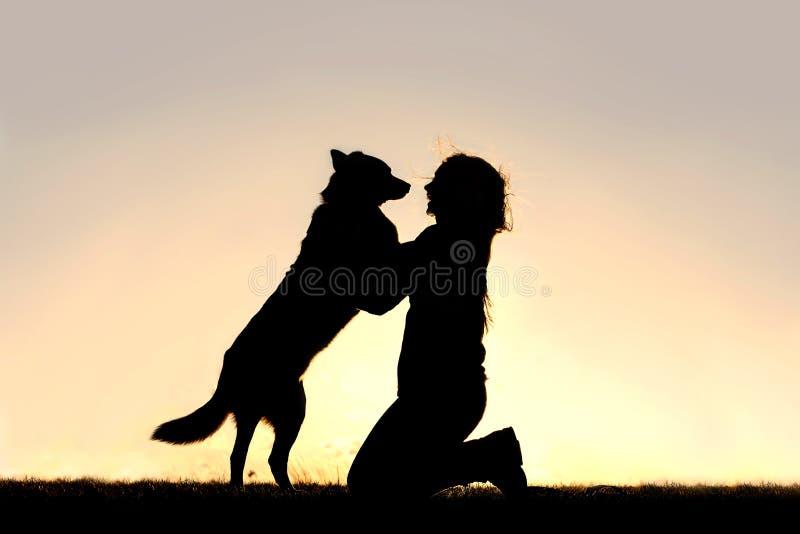Le chien heureux sautant jusqu'à saluent la silhouette de femme image stock