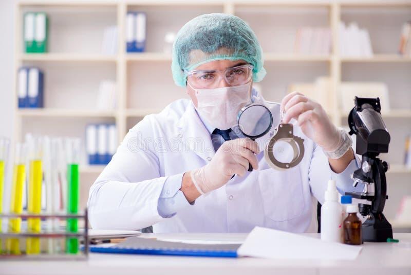 Le chimiste de police de criminaliste regardant des preuves de crime photographie stock