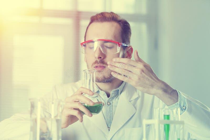 Le chimiste de scientifique inhale le parfum de ses flacons images stock