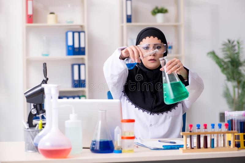 Le chimiste f?minin dans le hijab fonctionnant dans le laboratoire images libres de droits