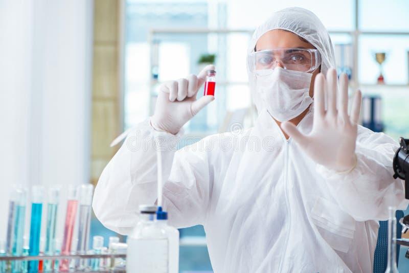 Le chimiste travaillant dans le laboratoire avec les produits chimiques dangereux image stock