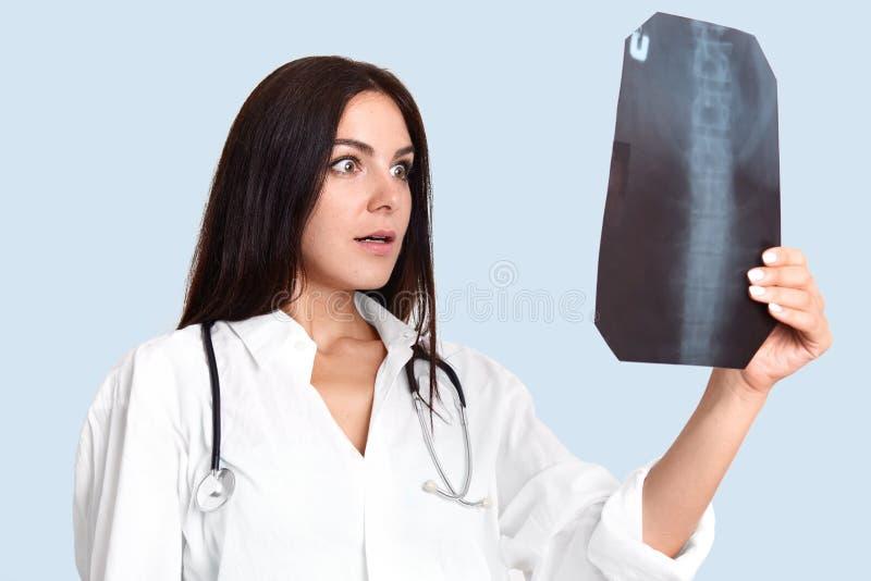 Le chirurgien féminin examine le rayon de X, regarde l'épine dorsale, choquée avec le résultat Le radiologue de femme dans la cor photographie stock libre de droits