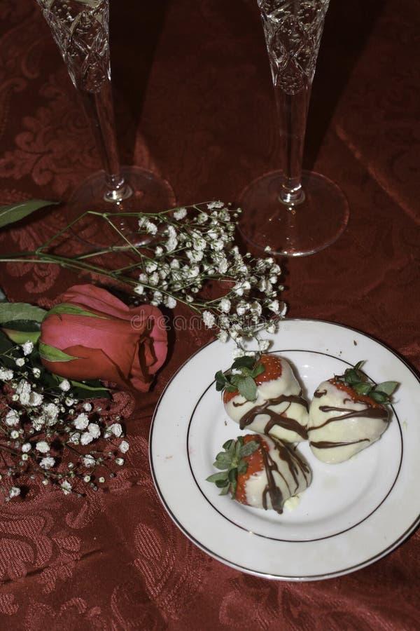 Le chocolat blanc a couvert les fraises, rose et le champagne images stock