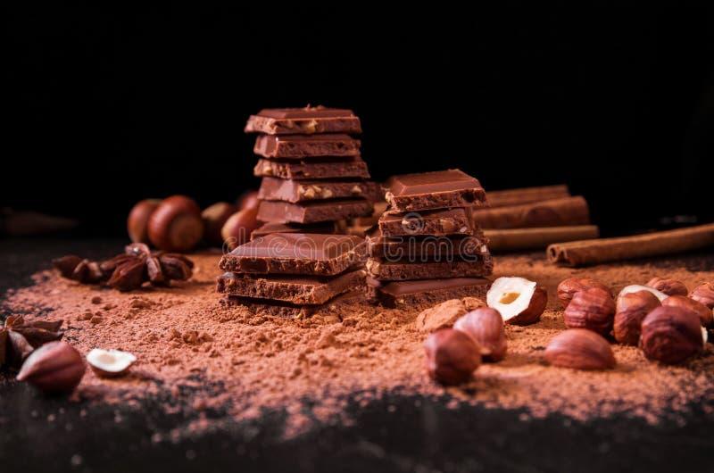Le chocolat rapièce avec la poudre, les écrous et la cannelle de cacao sur le fond foncé images libres de droits
