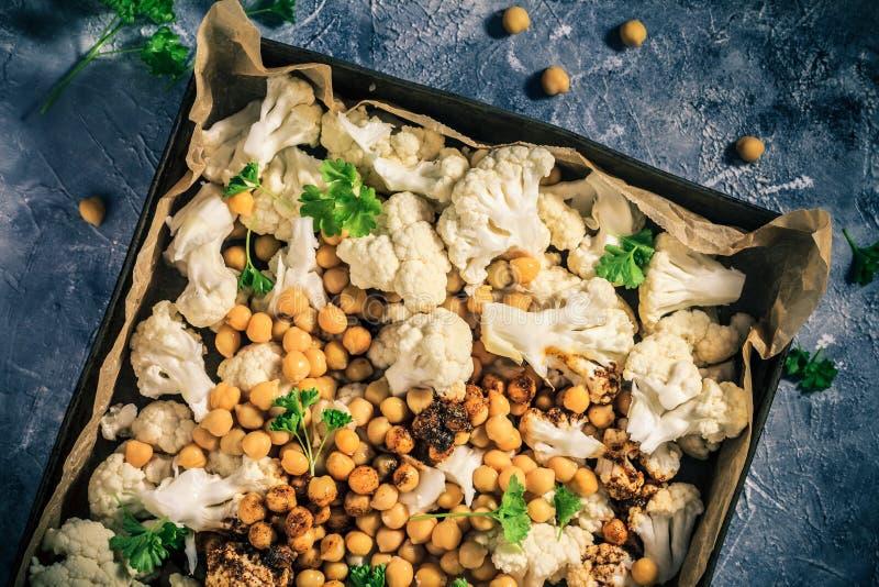 Le chou-fleur de plat végétarien d'ingrédients a fait des pois chiches cuire au four photo libre de droits