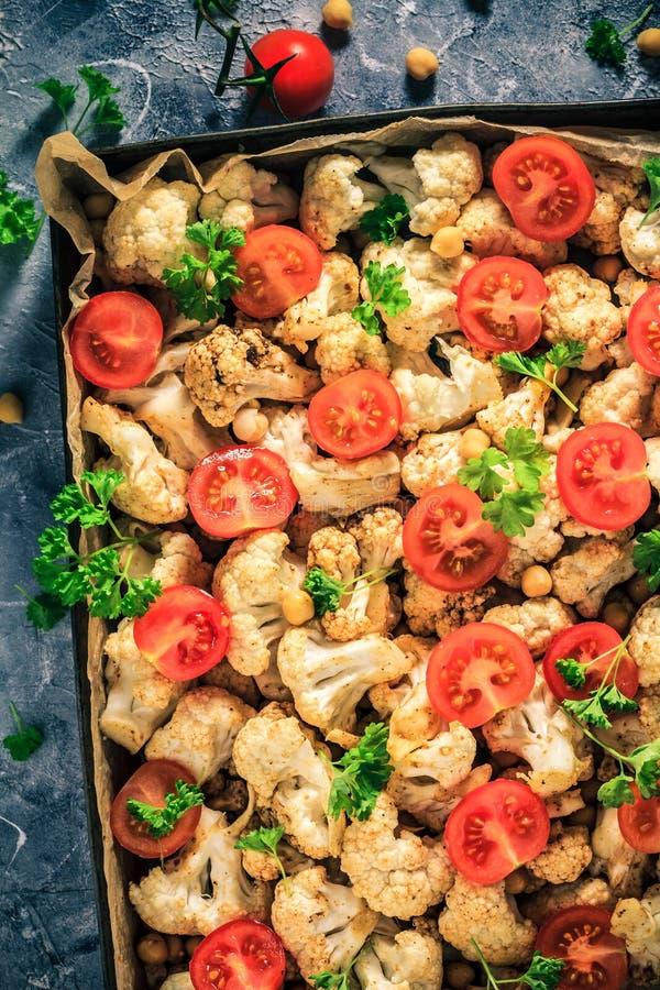 Le chou-fleur de plat de Vegan a fait des tomates cuire au four de pois chiches photo stock