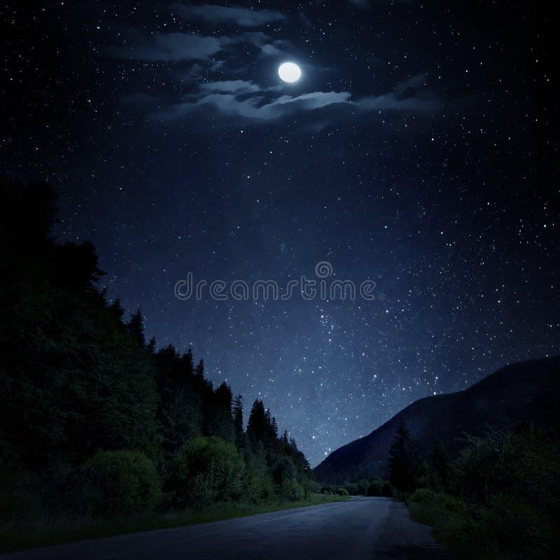 Le ciel étoilé, lune et la route de montagne par nuit photo libre de droits