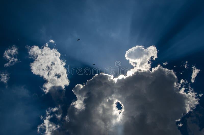Le ciel bleu et le soleil couverts de nuage de couleur grise images libres de droits