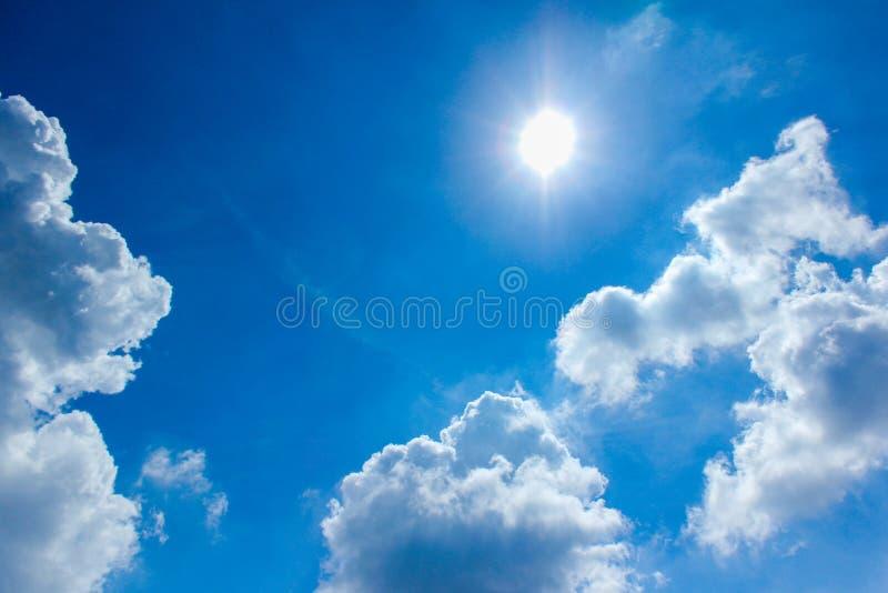 Le ciel bleu opacifie le soleil lumineux photographie stock libre de droits