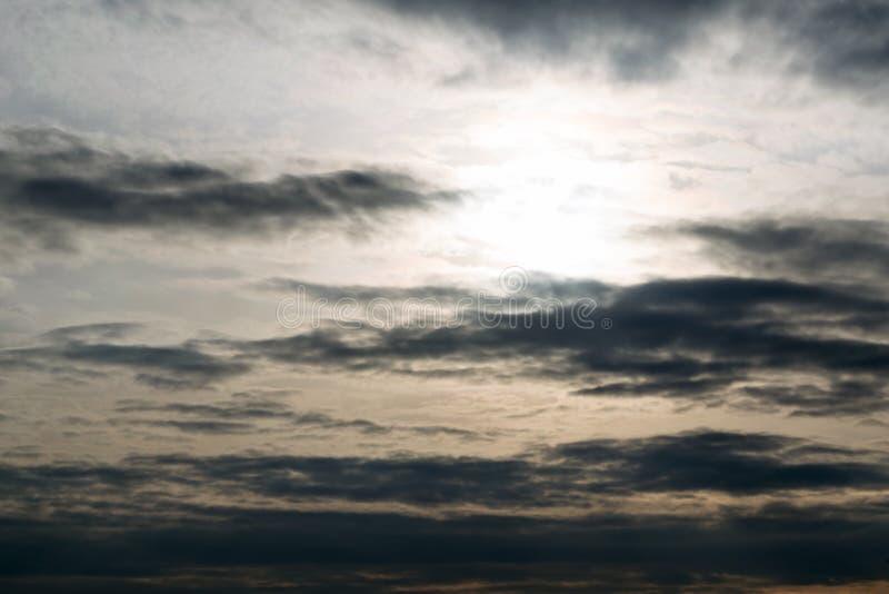 Le ciel foncé, le soleil de soirée, les nuages dans une ligne le long de l'horizon images stock