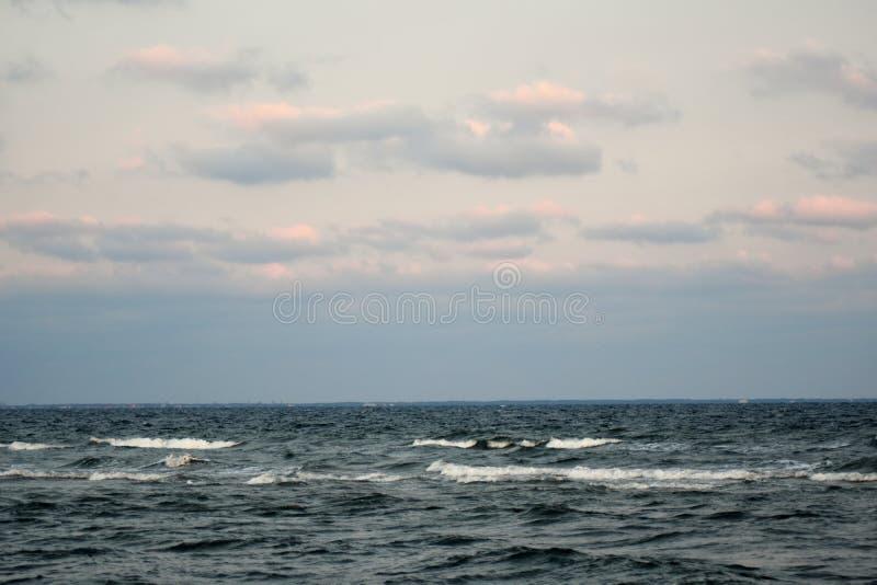 Le ciel nuageux dramatique au-dessus de la mer baltique au coucher du soleil images stock