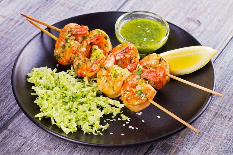 Le Cilantro a grillé des crevettes sur des brochettes avec le chou de napa de sésame, la sauce verte à beurre et le citron Crevet photos stock