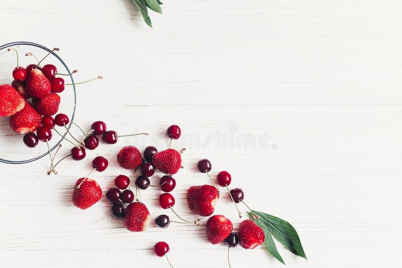 Le ciliege e le fragole fresche hanno sparso dalla ciotola su Rus bianca fotografie stock libere da diritti