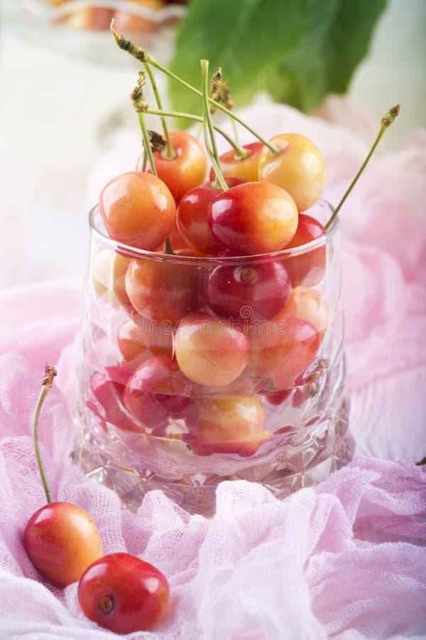 Le ciliege fresche in vetro trasparente hanno messo sopra la tavola di legno immagini stock libere da diritti