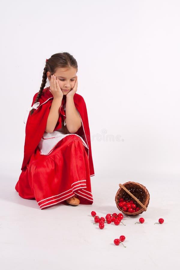 Le ciliege rovesciate bambina è tristi fotografia stock libera da diritti