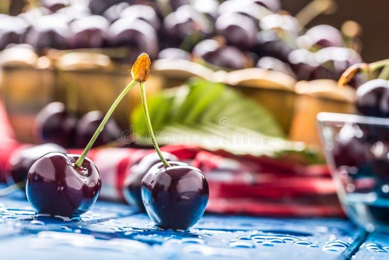Le ciliegie mature sul blu woden la tavola con le gocce di acqua immagine stock