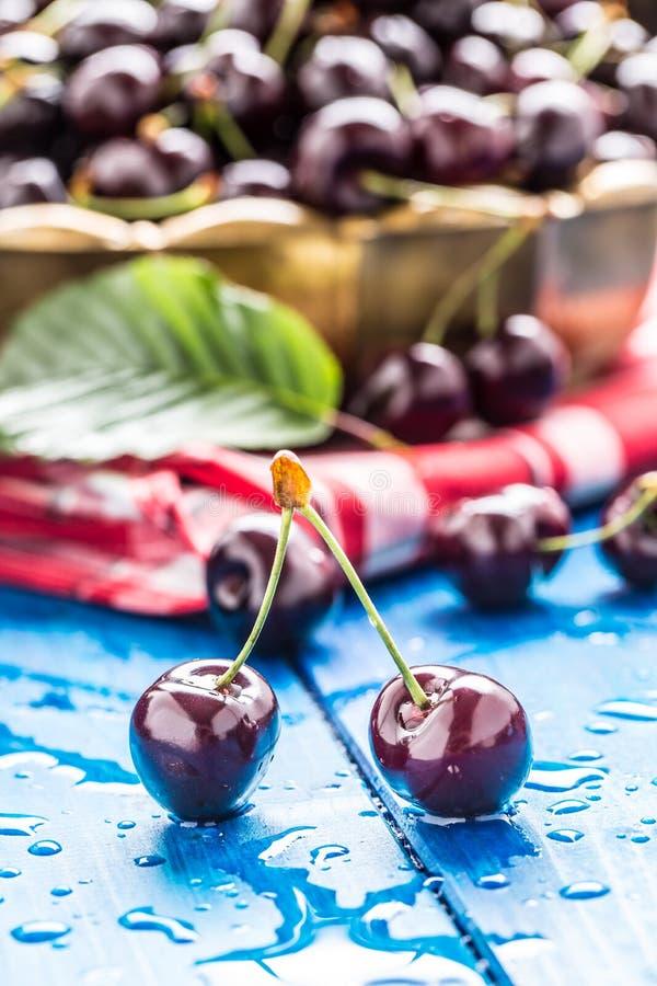 Le ciliegie mature sul blu woden la tavola con le gocce di acqua immagini stock