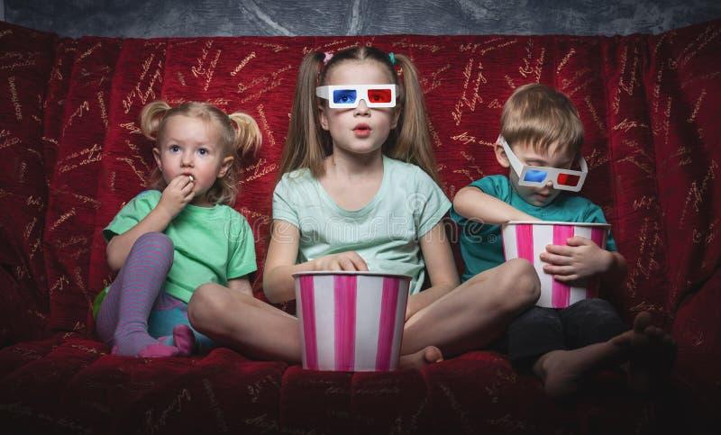 Le cinéma des enfants : Les enfants s'asseyent sur un sofa rouge et observent un film 3D photographie stock libre de droits
